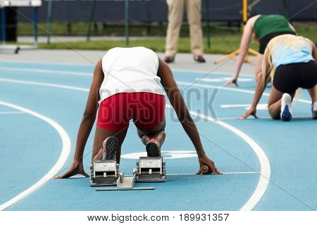 A high school female is in the starting blocks ready to start a relay race at a track and field competition