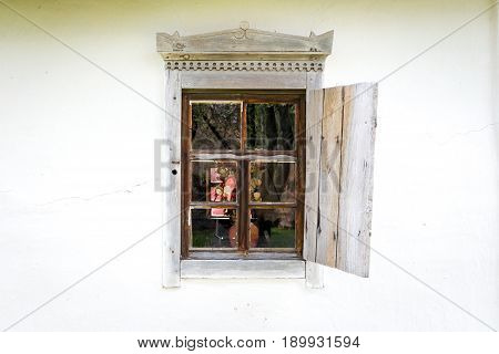 National Museum Pirogovo in the outdoors near Kiev. An old antique window with flowers in a vintage peasant white house in Ukraine. An antique wooden window frame with a door.