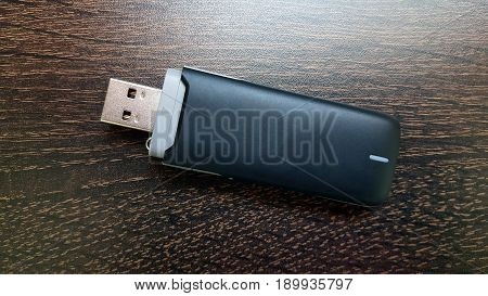 Black 3g usb wireless mobile modem on wooden background