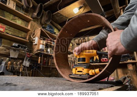 Carpenter grinding wooden drum shell from inside with sandpaper closeup