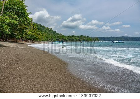 Unrecognizable Tourists enjoy the beach in Corcovado National Park beach and forest, Osa Peninsula, Costa Rica