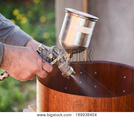 Carpenter spraying lacquer on wooden drum shell closeup