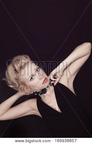 Portrait of a young blonde woman with beads on black background