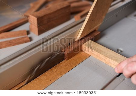 Circular saw sawing merbau wood brick closeup
