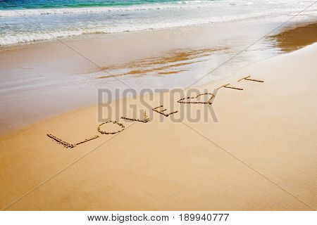 Word Love TT Trinidad and Tobago written on the beach sand in Maracas Bay Beach