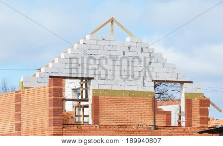 Building house construction with insulation for energy saving. Insulation House Attic Insulation Construction. Solid wall insulation with mineral wool. Energy efficiency house wall building.