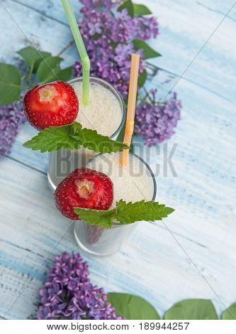 Milk smoothie with strawberries and banana on a blue wood background with lilac top view. . The vertical frame.