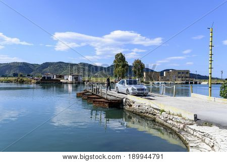BUTRINT, ALBANIA - MAY 18: Ferry with car crossing through Lake Butrint Bay on May 18, 2017 in Butrint, Albania.
