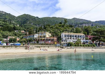 PALEOKASTRITSA, GREECE - MAY 15: Tourists enjoying the beautiful weather are relaxing on the beach on May 15, 2017 in Paleokastritsa resort, Corfu island in Greece.
