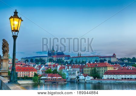 View of Prague Castle, mala Strana and Vltava river in Prague from Charles Bridge with street lamp during blue hour sunrise.