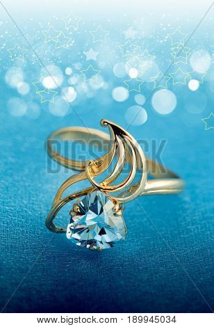 Elegant golden jewelry ring with blue topaz on blue background