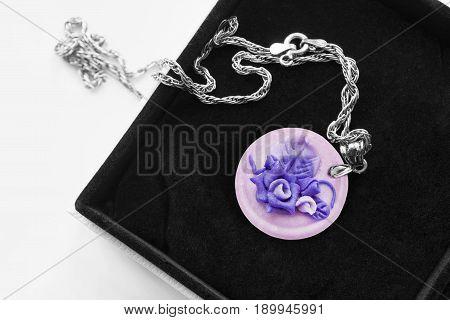 Vintage ceramic medallion with violet roses in black jewel box