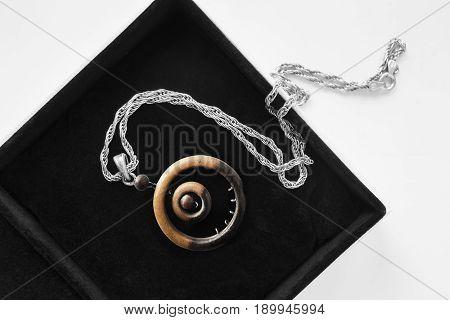 Wooden ethnic pendant on silver chain in jewel box closeup