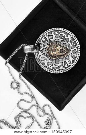 Ethnic silver medallion in black jewel box closeup