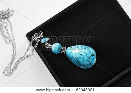 Vintage turquoise pendant on silver chain in jewel box closeup