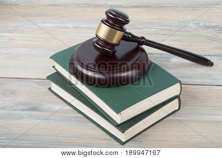 Books and wooden judges gavel on wooden background. Copy space for text. Law concept