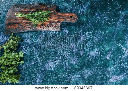 Fresh tarragon on the cutting board. Fresh cilantro, dill, oregano, thyme, lemon balm ready for cooking. Dark blue spotty background. Top view