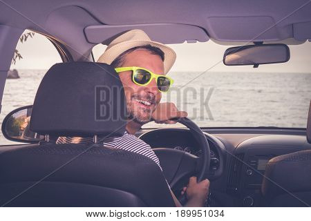 Young man at driver seat. Sea in the background. Tourism and on the road concepts.