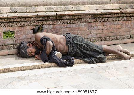 KATHMANDU NEPAL - SEPTEMBER 29 2016 : Poor sadhu holy man sleeping on the pavement in the Pashupatinath Temple Kathmandu. Nepal . Close up