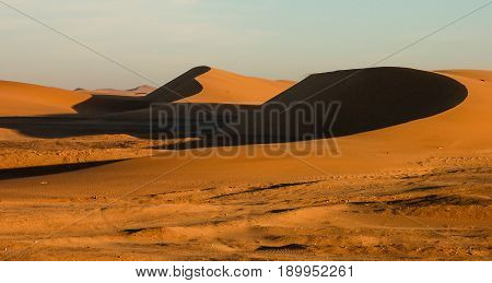 Two curving sand dunes in the midst of the desert. Sunlight position creates high contrast between rim of dune and the depressions.