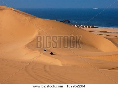 A small town sits at the edge of the Kalahari Desert on the Atlantic Ocean.  In the foreground are two dune buggies traversing the dunes.
