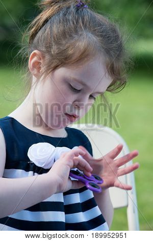 Young Girl Playing with popular fad trend Fidget Hand Spinner gadget