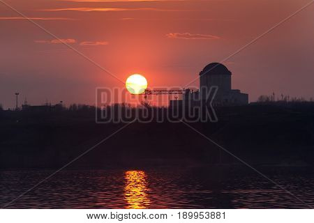 Crimson sunset at Voronezh water reservoir. Silhouette of nuclear power plant.
