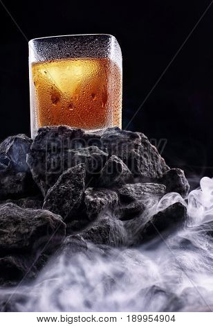 Glass Of Whiskey With Half Glass Ice .on Stone Mountain With Fog.creative Photo.advertising Shot