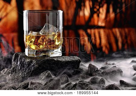 Glass Of Whiskey And Ice.creative Photo Glass Of Whiskey On Stone With Fog And Sunset Background.cop