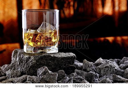 Glass Of Whiskey And Ice.creative Photo Glass Of Whiskey On Stone With Sunset Background.copy Space.