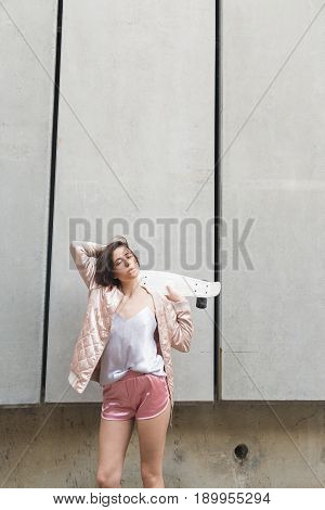Female skater walking in city with skateboard.Stylish brunette girll holding skateboard. Woman in pink sporty look