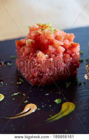 a beef tartar with avocado and tomatoes