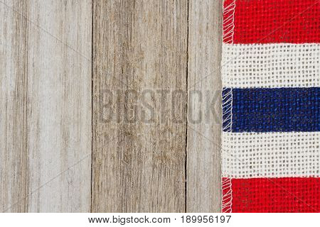 Red white and blue pip burlap ribbon on weathered wood background with copy space for your message