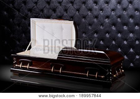 Opened wooden brown sarcophagus isolated on gray luxury background. casket, coffin on royalbackground. Ritual objects for burial. Conduct of the deceased on his last journey. Surrender body dust of the earth. Christian funeral ritual