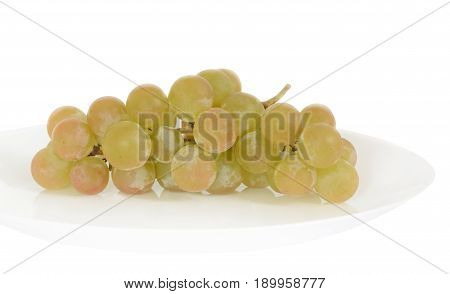 Cluster of green grapes on a white plate