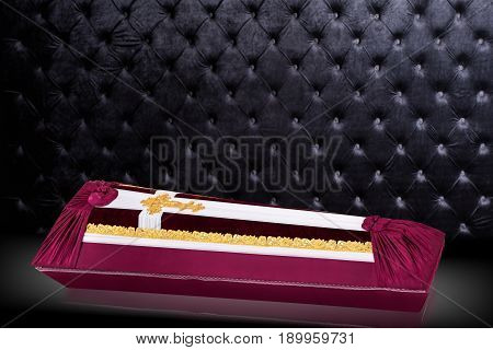 closed coffin covered with red and white cloth decorated with Church gold cross isolated on gray luxury background. Ritual objects for burial. Surrender body dust of the earth.