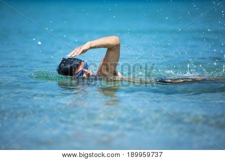 Young man swimming the front crawl in the sea (swimmer, triathlon)