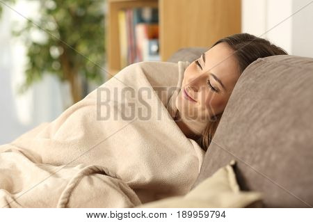 Relaxed girl sleeping covered with a warmly blanket sitting on a comfortable couch in the living room at home