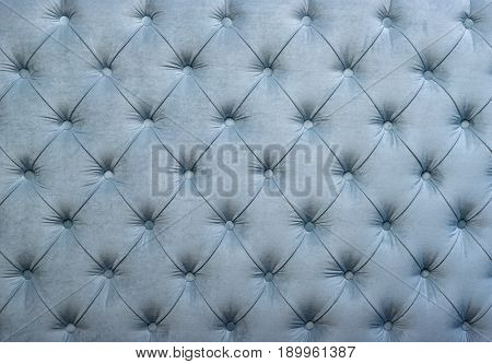 Light blue velvet capitone textile background retro Chesterfield style checkered soft tufted fabric furniture diamond pattern decoration with buttons close up