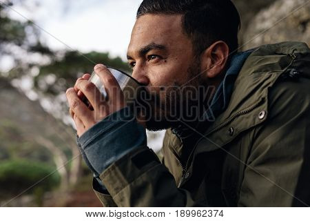 Close up shot of young man drinking hot coffee taking break during hiking. Male hiker taking rest outdoors.