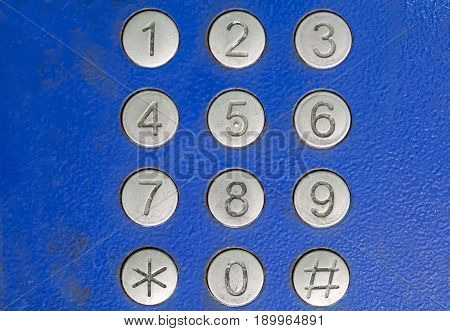 Street payphone. Digits for dialing a phone number. Blue background