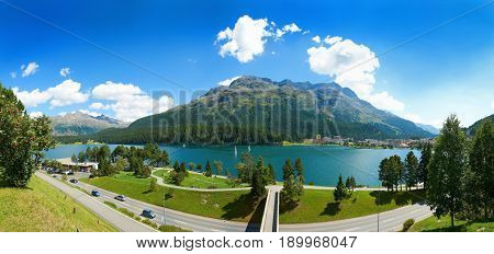 Panoramic view on Alpine green mountains, bridge, blue water lake, city streets and roads. Swiss panorama. Saint Moritz Swiss holidays vacations tours, tourists travels to Matterhorn