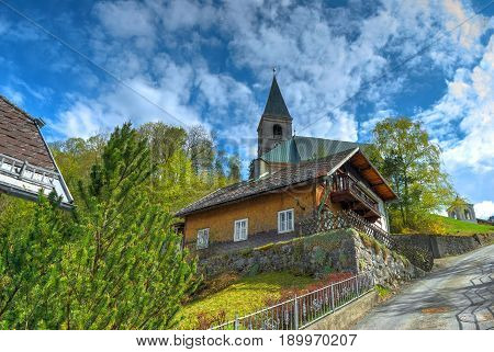 View on wooden stone church with bell tower among bloom green trees in Alpine mountains. Traditional Europe church architecture. Famous classic austrian church architecture. Diagonal view