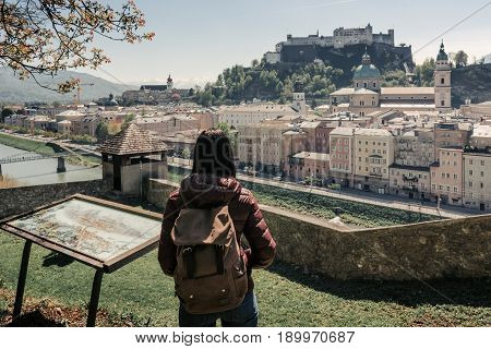 SALBURG, AUSTRIA - 21 APRIL 2016:  The girl tourist on the observation deck at the old maps of the city with views of the Hohensalzburg fortress