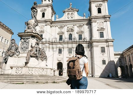 SALBURG, AUSTRIA - 21 APRIL 2016: Girl traveler with a backpack near the famous cathedral Salzburg (Salzburger Dom) at Domplatz Salzburg Land Austria