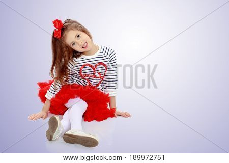 Portrait of a little girl in a bright red skirt with a red bow on his head.The girl sat down legs.Purple gradient background.