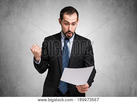 Very happy businessman reading a document