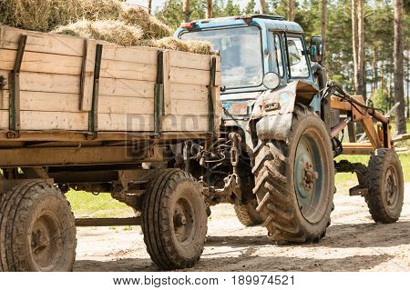 Tractor carries a trailer with bales of hay