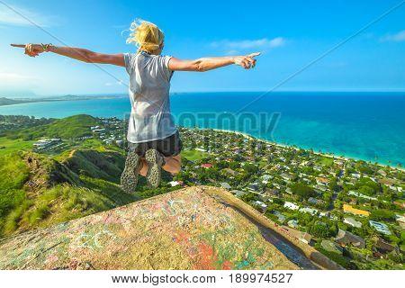 Happy hiker jumping. Hawaiian hiking by popular Lanikai Pillbox Hike offering spectacular views of Lanikai Beach, Mokulua Islands and Kailua Beach. Traveler freedom woman. Oahu East shore, Hawaii, USA