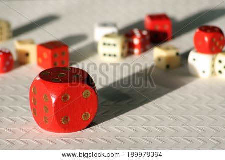 Large red dice with smaller red and white dice, casting shadows on the luck of the roll.